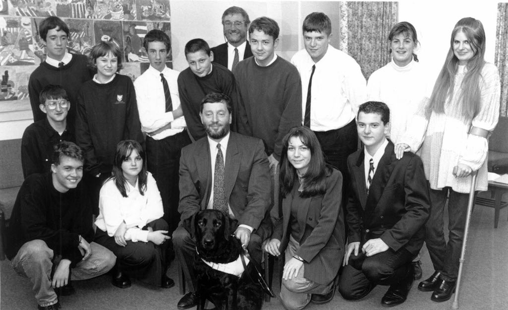 Shadow education minister David Blunkett pictured with his guide dog Lucy, headmaster David Robinson and students during the politician's visit to Penrith's Ullswater Community College in 1995.