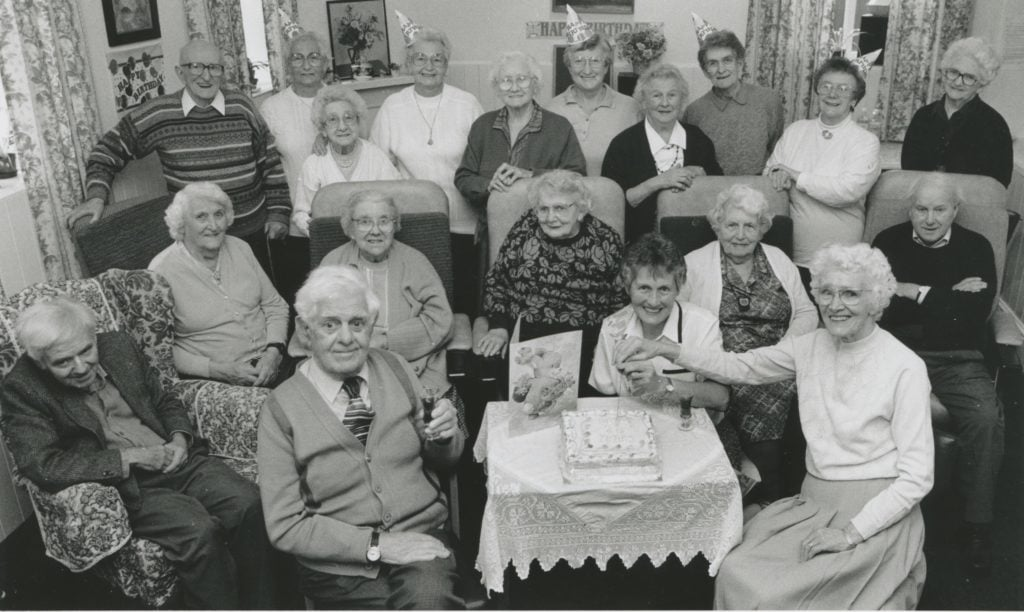 Herbert Cole and Mrs. Louie Strong cut a birthday cake to mark the 20th anniversary of the Penrith day care centre in 1995, assisted by day care co-ordinator Joyce Allen and watched by centre members.