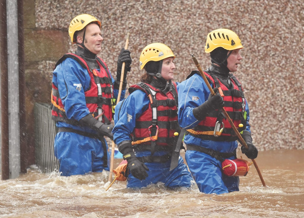 Firefighters Tony Haworth, Kate Farrance and JasonDeakin look for stranded residents in Appleby.