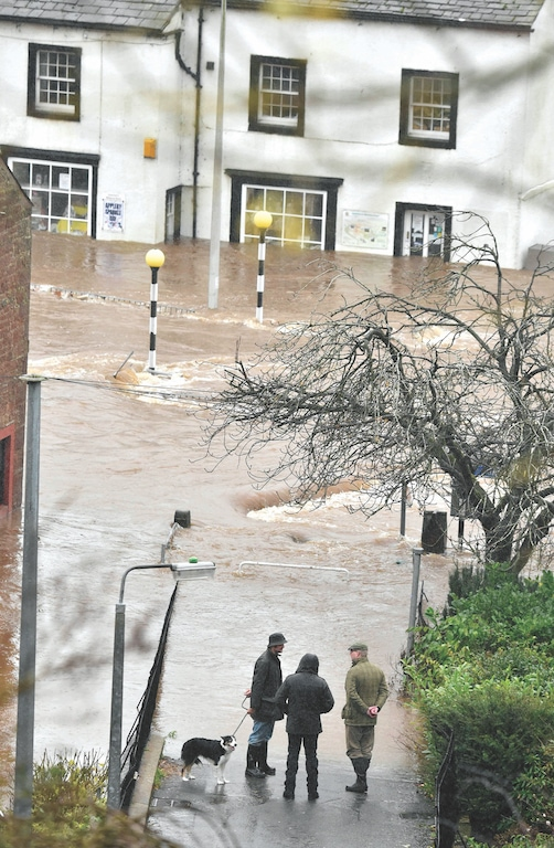 People watch the floodwater running through Appleby.