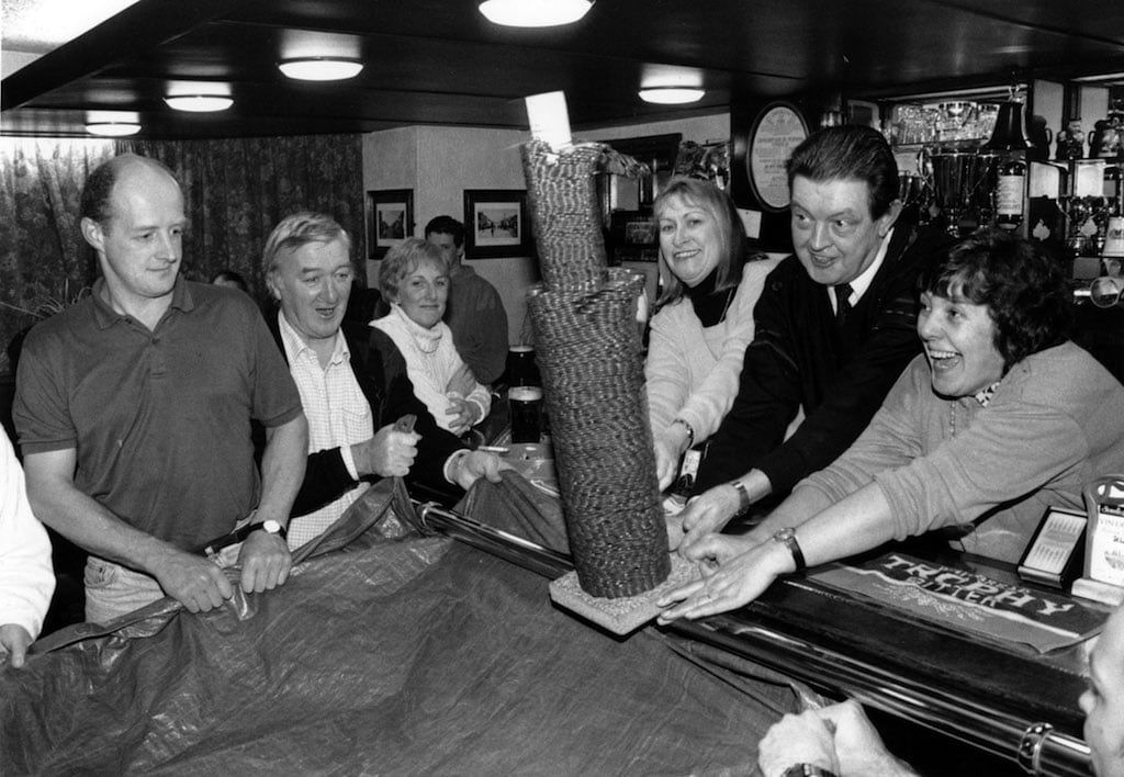 Watched by locals at the Golden Fleece, Brough, Corinthe Newman, organiser in Cumbria for the Royal National Institute for the Blind, and licensees Gordon and Anne Stott demolish a pile of pennies built up on the bar by customers.