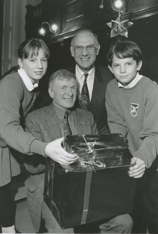 Spen Glover receives a circular saw from Katie Woan and Patrick Duckworth, on behalf of parents and pupils at Beaconside Junior School, Penrith, to mark his retirement from the position of deputy head 25 years ago. Looking on is deputy head Geoffrey Dredge.