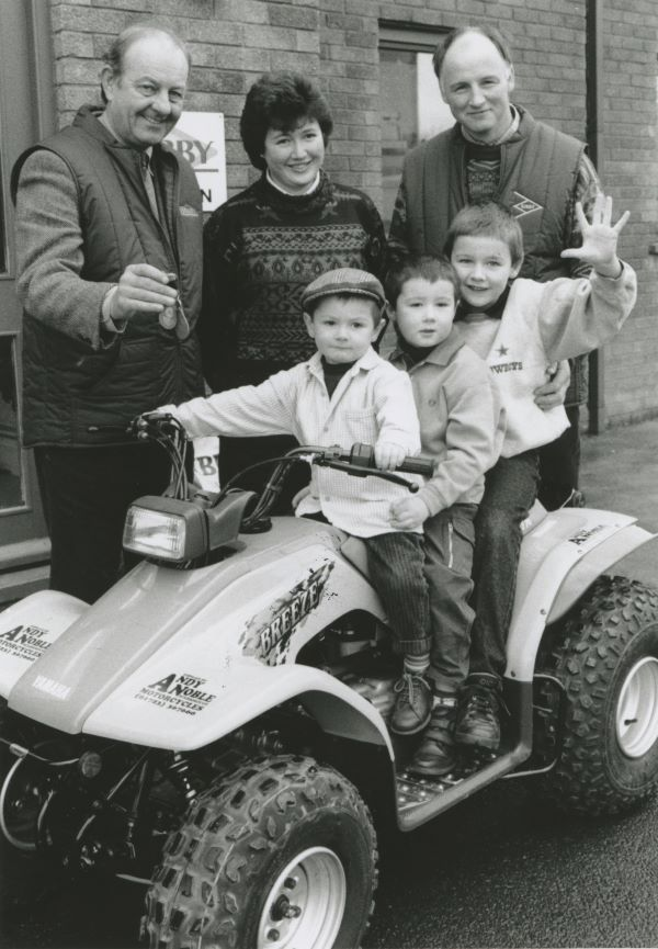John Atkinson, district manager for J. Bibby Agriculture, presents the keys of a new Yamaha ATV to Kate and Stephen Harrison, Aimshaugh, Alston, who won it in a draw held 25 years ago at the North West and Borders Sheep Fair. Trying it out are Kate and Stephen's children. Alistair, Oliver and Isaac.