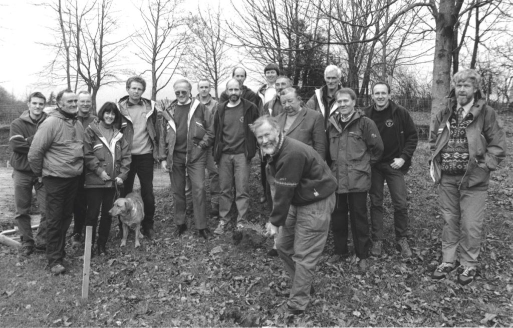 Watched by team members. Sir Chris Bonington cuts the first turf at the site of Keswick mountain rescue team's new base in 1996.