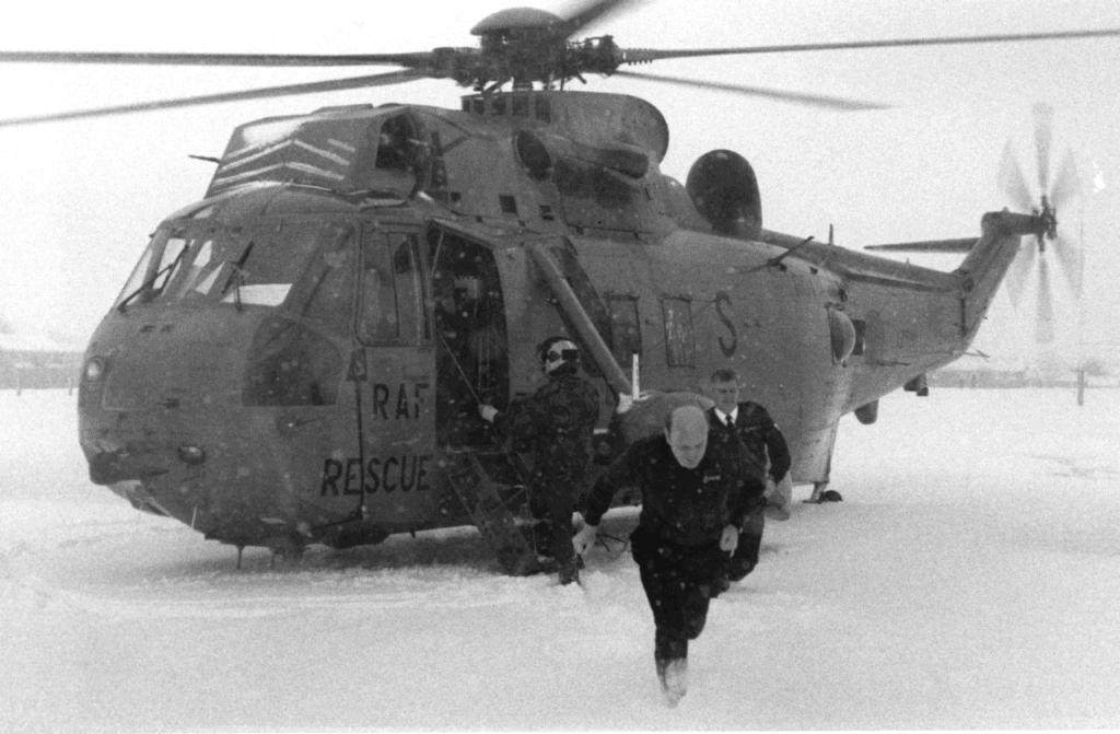 Penrith police officers return to their vehicles after escorting dialysis patient John Dent to an RAF helicopter to Carlisle for treatment during a spell of snowy weather
