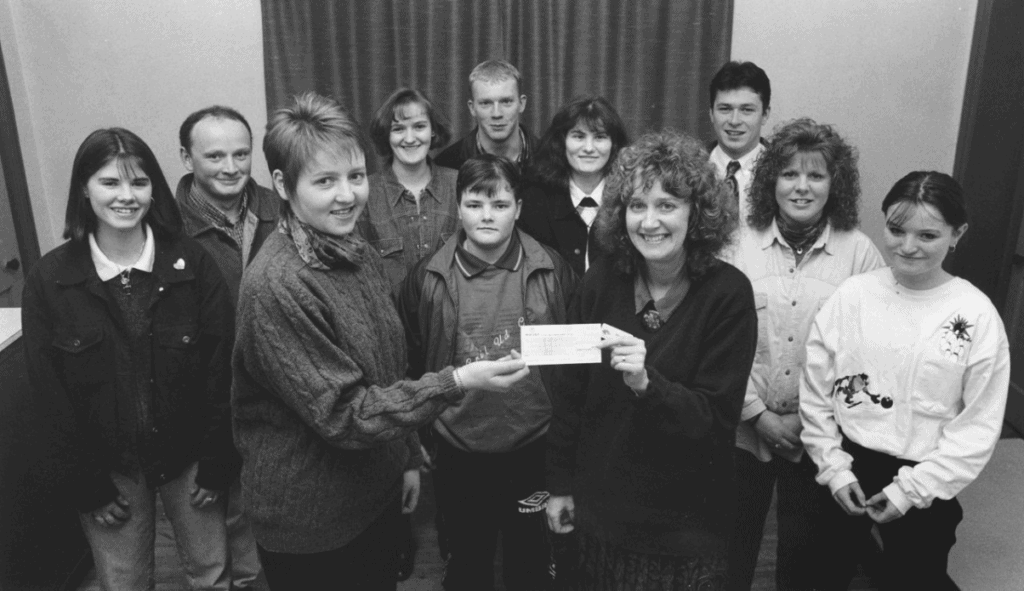 Caldbeck young farmers look on as club chairperson Rachel Patterson presents a £300 cheque to Margaret Ashton, of the East Cumbria Macmillan Nurses team. The money was raised at a coffee morning.